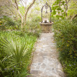 Beautiful Lush Park Walkway and Antique Well - Stock Photo