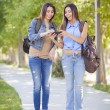 Young Adult Mixed Race Twin Sisters Sharing Cell Phone Experienc — Stock Photo