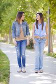 Unga vuxna blandras tvillingsystrar promenader tillsammans — Stockfoto