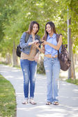 Unga vuxna blandras tvillingsystrar mobiltelefon erfarenhetsutbyte — Stockfoto