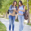 Young Adult Mixed Race Twin Sisters Sharing Cell Phone Experienc — Stock Photo #25190045