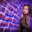 Frightened Pretty Young Woman Against Brick Wall at Night — Stock Photo