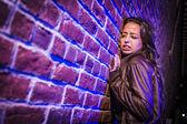 Przestraszony całkiem młoda kobieta przed murem w nocy — Zdjęcie stockowe