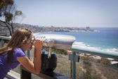 Young Girl Looking Out Over the Pacific Ocean with Telescope — Stock Photo
