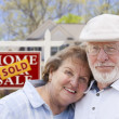Senior Couple in Front of Sold Real Estate Sign and House — 图库照片
