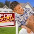 Stock Photo: Mixed Race Father and Son In Front of Real Estate Sign and House