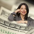 Hispanic Woman Leaning on a One Hundred Dollar Bill — Stock Photo #27795095