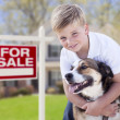 Young Boy and His Dog in Front of For Sale Sign and House — Stock Photo #28005319
