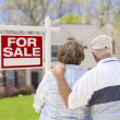 Happy Senior Couple Front of For Sale Sign and House — Stok Fotoğraf #28005065