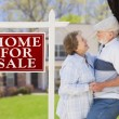 Happy Senior Couple Front of For Sale Sign and House — Stok Fotoğraf #28005085