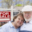 Happy Senior Couple Front of For Sale Sign and House — Stock Photo #28005185