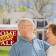 Senior Couple in Front of Sold Real Estate Sign and House — Stock fotografie