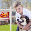 Stock Photo: Young Boy and His Dog in Front of Sold For Sale Sign and House