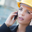 Worried Female Contractor Wearing Hard Hat on Site Using Phone — Stock Photo #28368945