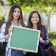 Mixed Race Female Students Holding Blank Chalkboard — Stock Photo