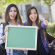 Mixed Race Female Students with Thumbs Up Holding Blank Chalkboa — Stock Photo #29405659