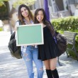Excited Mixed Race Female Students Holding Blank Chalkboard — Stock Photo #29405675