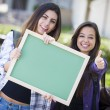 Mixed Race Female Students with Thumbs Up Holding Blank Chalkboa — Stock Photo