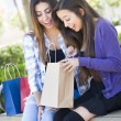 Young Adult Mixed Race Women Looking Into Their Shopping Bags — Stock Photo