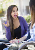 Expressive Young Mixed Race Female Sitting and Talking with Girl — Stock Photo