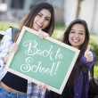 Mixed Race Female Students Holding Chalkboard With Back To Schoo — Stock Photo #29622911