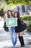 Mixed Race Female Students Holding Chalkboard With A Written — Foto Stock