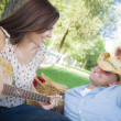 Mixed Race Couple with Guitar and Cowboy Hat in Park — Stock Photo #30634401