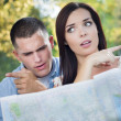 Lost and Confused Mixed Race Couple Looking Over Map Outside — Stock Photo #30698037