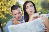 Lost and Confused Mixed Race Couple Looking Over Map Outside — Stock Photo