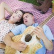 Mixed Race Couple at the Park Playing Guitar and Singing — Stock Photo