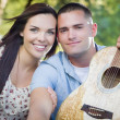 Mixed Race Couple Portrait with Guitar in Park — Stock Photo