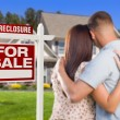 Military Couple Standing in Front of Foreclosure Sign and House — Stock Photo #30901153