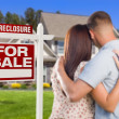 Military Couple Standing in Front of Foreclosure Sign and House — Stok fotoğraf