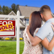 Sold For Sale Sign with Military Couple Looking at House — Stock Photo
