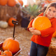 Stock Photo: Cute Girl Choosing Pumpkin