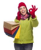 Kobieta mieszanej rasy torby na zakupy na telefon ok gestur — Zdjęcie stockowe