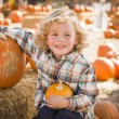 Little Boy Sitting and Holding His Pumpkin at Pumpkin Patc — Stock Photo