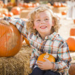 Little Boy Sitting and Holding His Pumpkin at Pumpkin Patc — Stock Photo #33543967