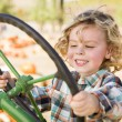 Adorable Young Boy Playing on an Old Tractor Outside — Stok fotoğraf