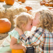 Sweet Little Boy Kisses His Baby Sister at Pumpkin Patc — Stock Photo