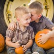 Two Boys Sitting Against Tractor Tire Holding Pumpkins Whisperin — Stock Photo