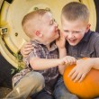 Two Boys Sitting Against Tractor Tire Holding Pumpkins Whisperin — Stock Photo #33670643