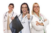 Three Female Doctors or Nurses with Thumbs Up Holding X-ray — Stock Photo