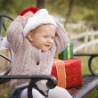 Young Child Wearing Santa Hat Sitting with Christmas Gifts Outsi — 图库照片