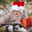 Young Child Wearing Santa Hat Sitting with Christmas Gifts Outsi — ストック写真