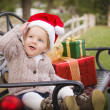 Young Child Wearing Santa Hat Sitting with Christmas Gifts Outsi — Lizenzfreies Foto