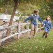 Happy Young Brother and Sister Running Outside — Stock Photo