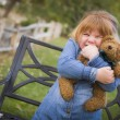 Cute Smiling Young Girl Hugging Her Teddy Bear Outside — Stock Photo