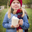 Cute Young Girl Holding Cocoa Mug with Marsh Mallows Outside — Stock Photo #35881287