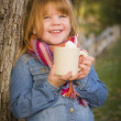 Cute Young Girl Holding Cocoa Mug with Marsh Mallows Outside — Stock Photo #35881493